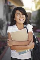glücklicher junger Schüler geht zur Schule foto