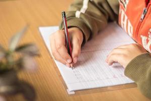 Schüler der ersten Klasse schreibt Briefe in ein Notizbuch