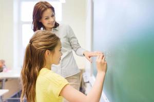 kleines lächelndes Schulmädchen, das auf Kreidetafel schreibt foto