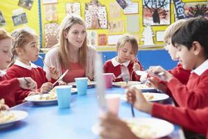 Schulkinder mit Lehrer am Tisch sitzen foto