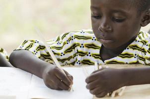schwarzer Junge, der in der Schule zeichnet und schreibt foto