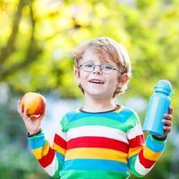 kleiner Schuljunge mit Büchern, Apfel und Trinkflasche foto