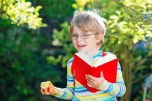 kleiner Junge mit Apfel auf dem Weg zur Schule foto