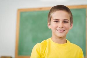 lächelnder Schüler, der in einem Klassenzimmer sitzt foto