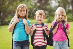 lächelnde Klassenkameraden mit Schultaschen foto
