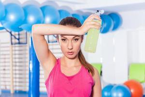 junges Mädchen trinkt isotonisches Getränk, Fitnessstudio. Sie wischt sich den Schweiß ab foto