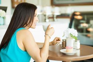 glückliches Mädchen, das Kaffee trinkt foto