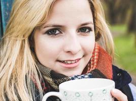 Herbstfrau, die Kaffee trinkt.