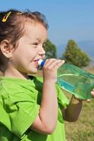 kleines Mädchen Trinkwasser foto