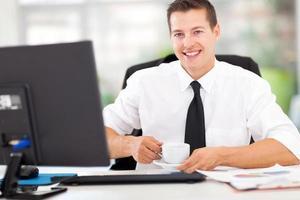 junger Büroangestellter, der Kaffee trinkt foto