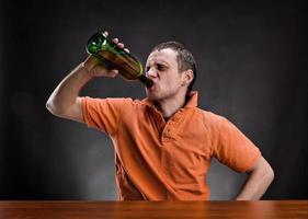 Mann trinkt Alkohol über grau foto