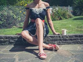 Frau, die Tee im Garten trinkt foto