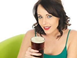 attraktive junge Frau, die Bier trinkt foto