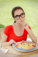 nachdenkliche Frau misst Pizza mit Maßband foto