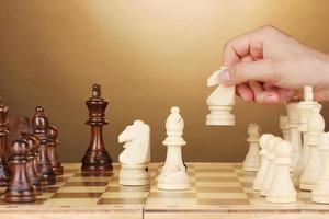 Schachbrett mit Schachfiguren auf braunem Hintergrund foto