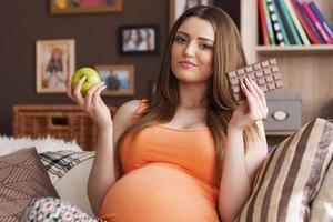 schwangere Frau unter Berücksichtigung der Wahl von gesunden und ungesunden Lebensmitteln foto