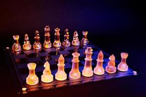 Glasschach auf Schachbrett beleuchtet von blauem und orangefarbenem Licht foto