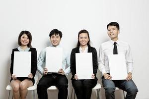 Das chinesische Business-Team hält leere Karten hoch. foto