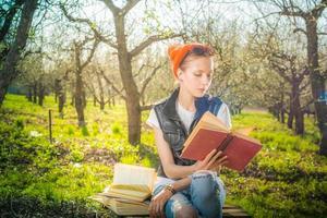 Frau im Park im Freien mit Tablette und Buch entscheiden, was
