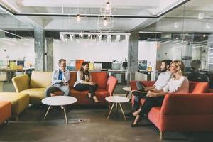 Gruppe junger Leute, die im modernen Café sprechen foto