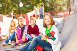 Mädchen sitzt vorne mit Skateboard und anderen Kindern foto