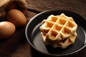 gebackene Waffeln in der Teflonpfanne und Eier auf Holz