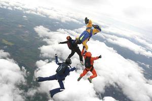 Vier Fallschirmspringer springen aus einem Flugzeug foto