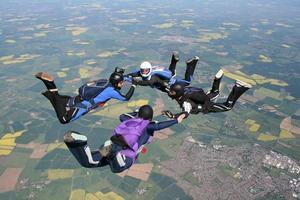 vier Fallschirmspringer im freien Fall Händchen haltend foto