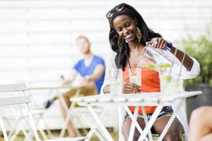 attraktive schwarze Frau, die an einem Kaffeetisch draußen sitzt foto