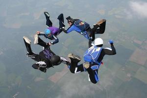 vier Fallschirmspringer bilden einen Kreis foto