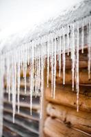 lange Eiszapfen schmelzen von einem Dach