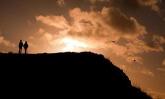 Mannsilhouette auf dem bunten Himmel während des Sonnenuntergangs.