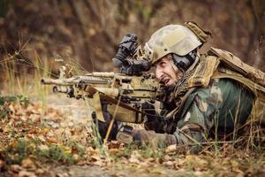 Soldat zielt auf ein Ziel von Waffen foto