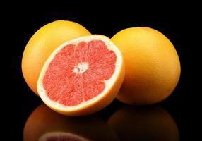 Studioaufnahme geschnitten drei Grapefruits isoliert schwarz foto