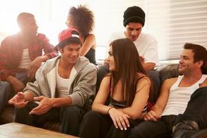 Gruppe junger Leute, die auf dem Sofa sitzen und sprechen