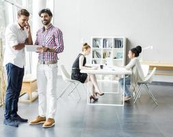 Gruppe junger Leute, die in einem hellen Raum arbeiten foto