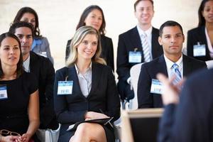 Delegierte, die auf der Konferenz dem Redner zuhören foto