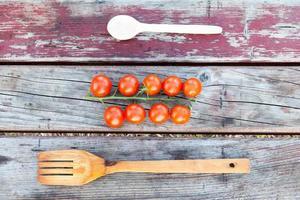 Holzgabel und Löffel mit Tomaten foto