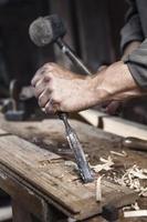 Hände des Zimmermanns mit Hammer und Meißel