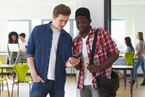 zwei männliche Studenten, die Handy im Klassenzimmer betrachten foto
