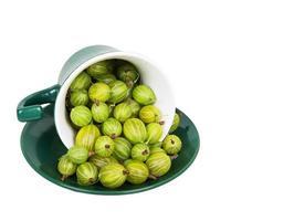 Stachelbeeren in einer umgekehrten grünen Tasse foto