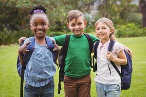 glückliche Schüler, die Schultaschen tragen foto