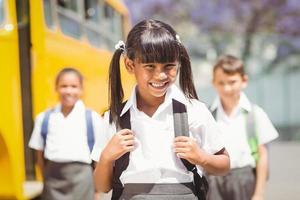 niedlicher Schüler, der in der Kamera durch den Schulbus lächelt foto