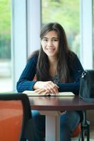 glücklicher junger Student, der in der Schule studiert foto