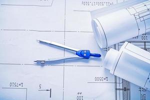 Kompass und zwei aufgerollte weiße Blaupausen horizontale Version foto