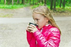 süßes Mädchen, das Getränk trinkt foto