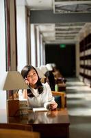 Frau liest Buch in der Bibliothek foto