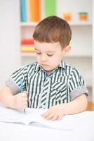 kleiner Junge zeichnet auf weißem Papier