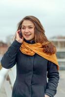 Frau im orangefarbenen Schal spricht am Telefon foto