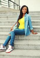 schöne glückliche lächelnde afrikanische Frau, die ein Jeanshemd und trägt foto